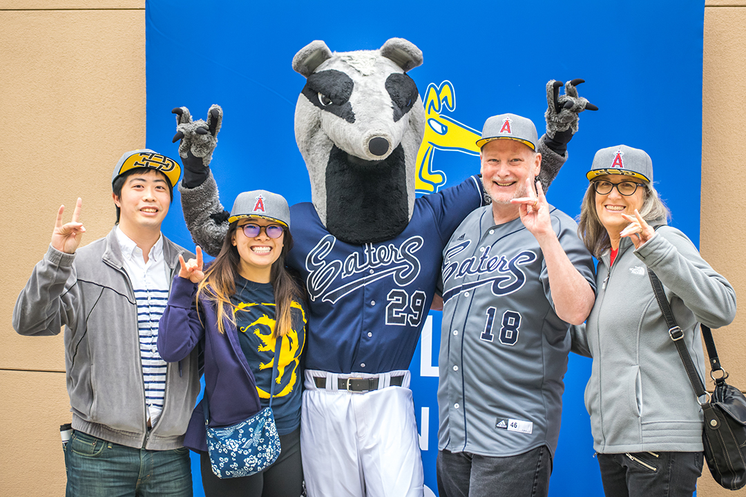 Chancellor Gillman with wife, Peter the Anteater and UCI students.